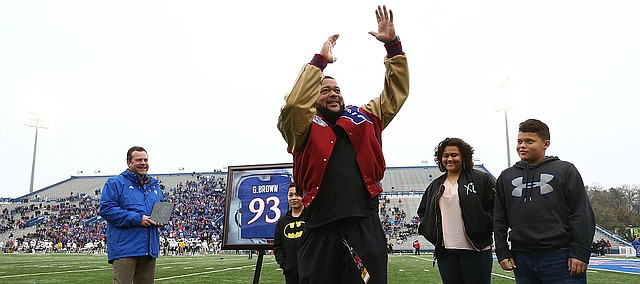 Kansas football great Gilbert Brown performs his signature tackle celebration for the Memorial Stadium crowd during a ceremony unveiling his name in the ring of honor on Saturday, Sept. 4, 2017.