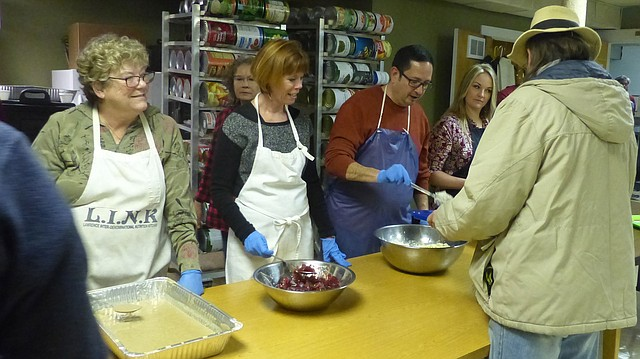 In this file photo from Nov. 28, 2016, Frank Ybarra serves a man during the annual LINK Thanksgiving dinner. Mary Olson, Janet Buie, Ybarra and Samantha Hauber were among about 150 volunteers who helped prepare, serve and deliver Thanksgiving meals for about 800 people.