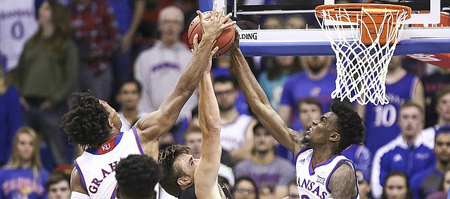 Kansas guard Lagerald Vick (2) and Kansas guard Devonte' Graham, left, stuff a shot from Fort Hays State forward Hadley Gillum (4) during the first half, Tuesday, Nov. 7, 2017 at Allen Fieldhouse.