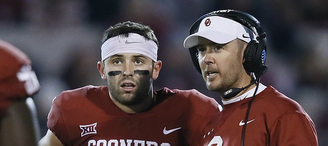 Oklahoma head coach Lincoln Riley, right, talks with quarterback Baker Mayfield (6) in the first quarter of an NCAA college football game against TCU in Norman, Okla., Saturday, Nov. 11, 2017. Oklahoma won 38-20. (AP Photo/Sue Ogrocki)