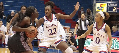 Kansas senior Chayla Cheadle (22) and junior Christalah Lyons (0) cut off the lane to the basket for Texas Southern's Breasia McElrath during the Jayhawks' 72-37 win on Wednesday at Allen Fieldhouse.