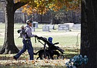 A man walks through Lawrence's Oak Hill Cemetery with a dog on a leash, Thursday, Nov. 16, 2017. The city parks and recreation department recently has received complaints about people allowing their dogs to run off leash in the cemetery.