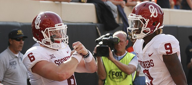 Oklahoma quarterback Baker Mayfield (6) celebrates a touchdown against Oklahoma State with teammate CeeDee Lamb (9) in the first half of an NCAA college football game in Stillwater, Okla., Saturday, Nov. 4, 2017. (AP Photo/Sue Ogrocki)