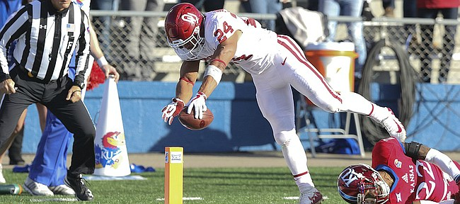 Oklahoma running back Rodney Anderson (24) reaches the ball over the goal line for a touchdown after leaving Kansas safety Tyrone Miller Jr. (22) on the turf during the first quarter on Saturday, Nov. 18, 2017 at Memorial Stadium.