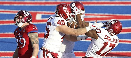 Kansas linebacker Joe Dineen Jr. (29) walks away as Oklahoma players celebrate with Oklahoma wide receiver Jordan Smallwood (17) following Smallwood's touchdown during the second quarter on Saturday, Nov. 18, 2017 at Memorial Stadium.