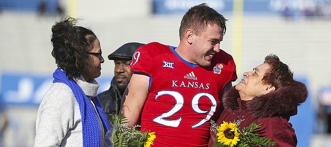 Kansas linebacker Joe Dineen Jr. (29) gets a thank you from Marialuz Cardenas, grandmother of Andre Maloney and Rosaelida Montoya, Maloney's mother after presenting them with flowers during the pregame Senior Day ceremony on Saturday, Nov. 18, 2017 at Memorial Stadium.