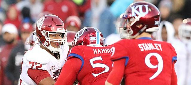 Oklahoma defensive lineman Amani Bledsoe (72) wrestles with Kansas offensive lineman Zach Hannon (56) during the third quarter on Saturday, Nov. 18, 2017 at Memorial Stadium.