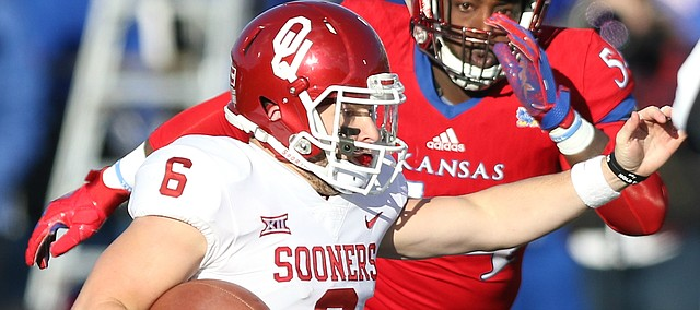 Oklahoma quarterback Baker Mayfield (6) looks to scramble as Kansas defensive tackle Jacky Dezir (54) closes in during the second quarter on Saturday, Nov. 18, 2017 at Memorial Stadium.