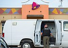 In this file photo from June 27, 2017, a law enforcement official works within a police van parked outside Taco Bell, 1220 W. Sixth Street following an early morning robbery.