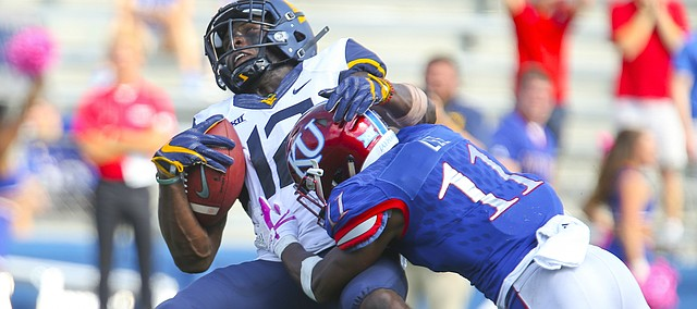West Virginia wide receiver Gary Jennings (12) is drilled by Kansas safety Mike Lee (11) after a deep catch during the fourth quarter on Saturday, Sept. 23, 2017 at Memorial Stadium.
