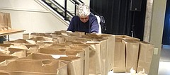 Alice King, of Lawrence, load pies Wednesday into paper bags to complete the LINK Thanksgiving meals to be delivered Thursday. She and her husband, Jim King, were among the volunteers who prepared a record 600 LINK meals a Maceli's for home delivery this year.
