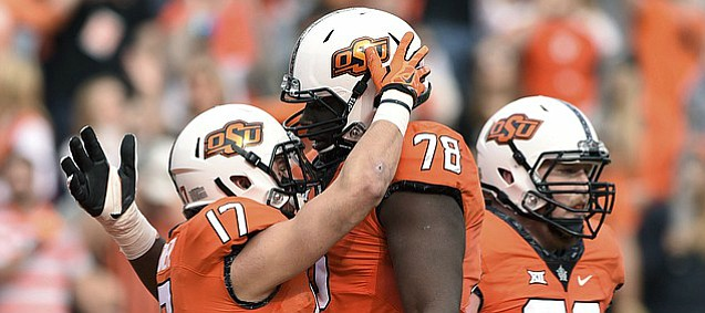 Oklahoma State wide receiver Dillon Stoner (17) celebrates his 76 yard touchdown with offensive linemen Aaron Cochran (78) and Johnny Wilson (72) during the first half of an NCAA college football game with Kansas in Stillwater, Okla., Saturday, Nov. 25, 2017.