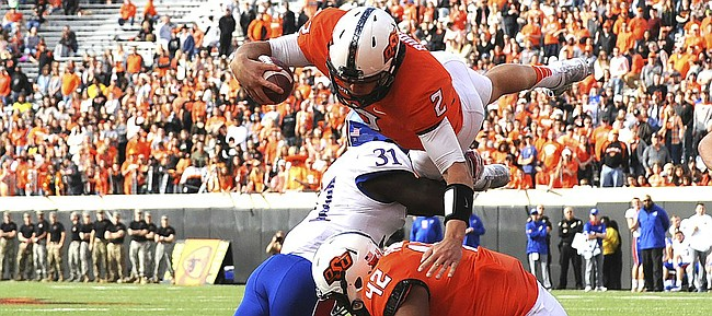 Oklahoma St quarterback Mason Rudolph (2) jumps over Kansas linebacker Osaze Ogbebor (31) and Oklahoma St tight end Sione Finefeuiaki for a touchdown during the third quarter of an NCAA college football game between Kansas and Oklahoma St in Stillwater, Okla., Saturday, Nov. 25, 2017. Rudolph ran for 2 touchdowns in the 58-17 win over Kansas.