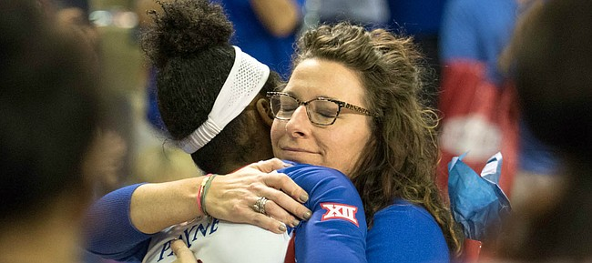 Kansas senior Kelsie Payne embraces associate head coach Laura Kuhn after a Senior Day match against West Virginia on Saturday, Nov. 25, 2017 at Horejsi Family Athletics Center.