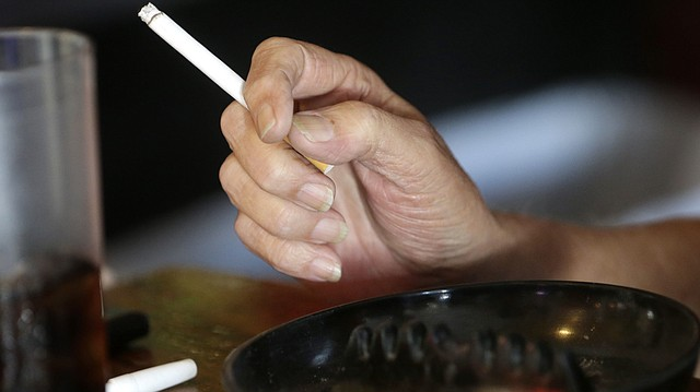 In this April 21, 2015, file photo, a patron smokes a cigarette inside a bar in New Orleans. Cigarette smoking, overeating and other unhealthy behaviors can be blamed for nearly half of U.S. cancer deaths each year, according to a new American Cancer Society study released Tuesday, Nov. 21, 2017. (AP Photo/Gerald Herbert, File)