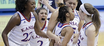KU teammates swarm around Kansas junior guard Christalah Lyons after a basket in the first half of the Jayhawks' 73-65 win over Rice at Allen Fieldhouse on Sunday.