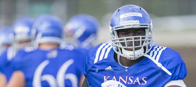 Kansas offensive lineman Hakeem Adeniji runs through warmups on Friday, Aug. 18, 2017 at the grass fields adjacent to Hoglund Ballpark.