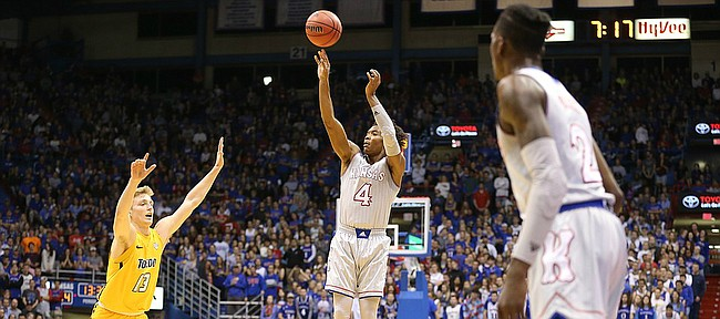 Kansas guard Devonte' Graham (4) puts up a three against Toledo guard Jaelan Sanford (13) during the first half on Tuesday, Nov. 28, 2017 at Allen Fieldhouse.