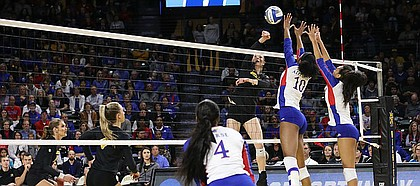Missouri right outside hitter Melanie Crow (1) spikes the ball over the Kansas blockers. Kansas lost to Missouri in five sets in the first round of the NCAA Championship in Charles Koch Arena on Dec. 1, 2017.