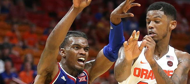Kansas guard Lagerald Vick (2) kicks a pass out to the wing while defended by Syracuse guard Frank Howard (23) during the second half, Saturday, Dec. 2, 2017 at American Airlines Arena in Miami.