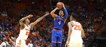 Kansas guard Devonte' Graham (4) pulls up for a three against Syracuse guard Frank Howard (23) and Syracuse guard Tyus Battle (25) during the second half, Saturday, Dec. 2, 2017 at American Airlines Arena in Miami.