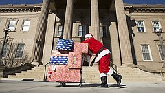 Graduate teaching assistants, David Cooper, Overland Park, Kan. pushes a dolly piled with Christmas presents to Strong Hall on Thursday, Dec. 7, 2017. The presents, carried messages asking members of the University of Kansas administration for improved compensation, benefits and resources. Cooper, along with other group members, marched the presents from Ecumenical Campus Ministries to Strong Hall over the lunch hour and delivered them outside the office of the chancellor.