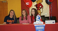 Lawrence High seniors, from left, Zoe Brewer, Morgan Husman and Katelyn Mask sign their letters of intent Wednesday. Brewer signed to Baker University (softball) while Husman (softball) and Mask (volleyball) both signed with Kansas City Kansas Community College.