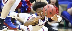 Kansas guard Devonte' Graham (4) tosses a ball from the floor as Washington forward Sam Timmins (33) hovers over during the second half, Wednesday, Dec. 6, 2017 at Sprint Center.