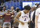 Kansas guard Devonte' Graham (4) and Kansas guard Sviatoslav Mykhailiuk (10) make their way off of the court as the Arizona State Sun Devils celebrate their 95-85 win over the Jayhawks on Sunday, Dec. 10, 2017 at Allen Fieldhouse.