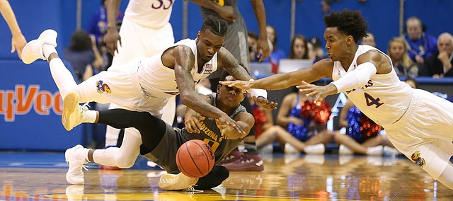 Kansas guard Lagerald Vick, center, and Kansas guard Devonte' Graham (4) dive on a loose ball with Arizona State guard Tra Holder (0) during the second half, Sunday, Dec. 10, 2017 at Allen Fieldhouse.