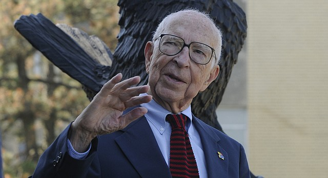 """In this file photo from 2008, Hal Sandy is pictured in front of a Jayhawk statue outside the Adams Alumni Center on the University of Kansas campus. Sandy created the """"happy"""" Jayhawk that is the basis for the university's current logo."""
