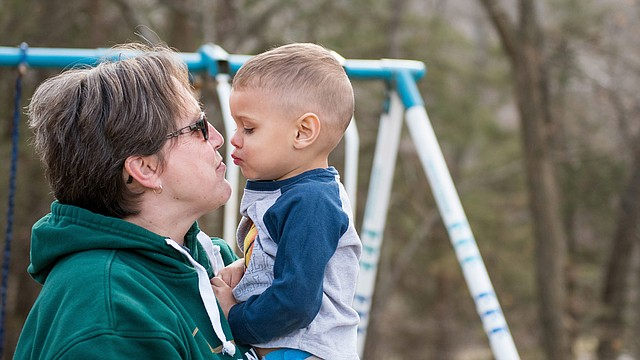 Karen Glotzbach and her grandson Zairean cuddle during a break from playing at Glotzbach's home.