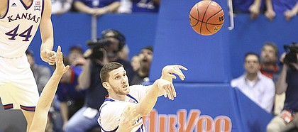 Kansas guard Sviatoslav Mykhailiuk (10) throws a pass from the floor after a steal from Omaha forward Matt Pile (40) during the first half on Monday, Dec. 18, 2017 at Allen Fieldhouse.