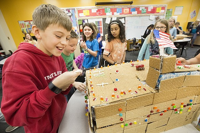 Sunflower Elementary fifth-graders Josh Lavin works to squeeze out some white icing to make a helicopter landing pad on the roof of a gingerbread likeness of Lawrence Memorial Hospital on Wednesday, Dec. 20, 2017 at the school. Several classes at the school participated in constructing gingerbread representations of Lawrence's iconic buildings and landmarks, which they later presented to pen pals via video. Also pictured next to Lavin are Lawrence Mccauley, Ava Kohart, Gabby Reed and Addison Norris.