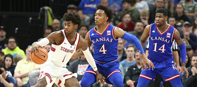 Kansas guard Devonte' Graham (4) defends against Stanford guard Daejon Davis (1) during the first half, Thursday, Dec. 21, 2017 at Golden 1 Center in Sacramento, California. At right is Kansas guard Malik Newman (14).