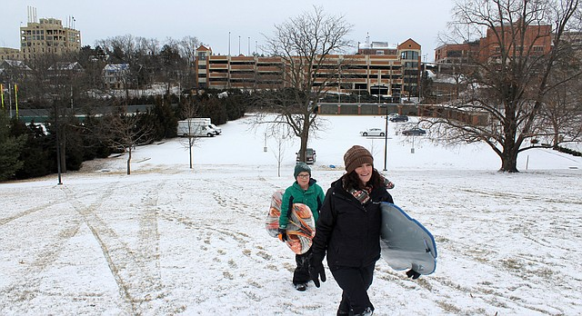 Kelly Sullivan and her son Jonah Owen, 11, try their luck at sledding near the Campanile on the University of Kansas campus on Tuesday. Lawrence received about a half-inch of snow, and forecasters are predicting cold weather throughout the week.