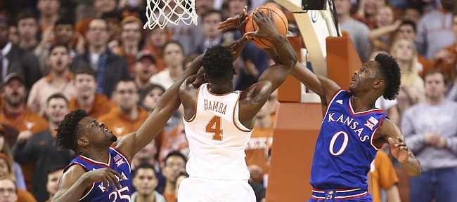 Kansas center Udoka Azubuike (35) and Kansas guard Marcus Garrett (0) strip a ball from Texas forward Mohamed Bamba (4) during the first half on Friday, Dec. 29, 2017 at Frank Erwin Center in Austin, Texas.
