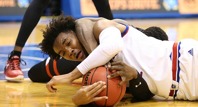 Kansas guard Devonte' Graham (4) gets caught in a stranglehold by Texas Tech center Norense Odiase (32) while tied up for a loose ball during the first half, Tuesday, Jan. 2, 2018 at Allen Fieldhouse.