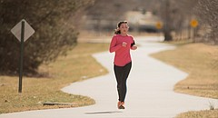 Lawrence resident MacKenzie Koester approaches 11th Street while running along the Burrough's Trail, Thursday, March 2, 2017. A local work group has started a campaign to fill the gaps in the Lawrence Loop in places where the multiuse path is interrupted. Eleventh and Oregon streets is one of those locations.