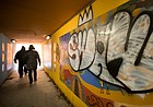 Pedestrians use the underground tunnel below Sixth Street connecting the Pinckney and Old West neighborhoods, Thursday, Jan. 4, 2018. The tunnel and parts of the mural that decorate its walls were vandalized with graffiti over the holiday break.