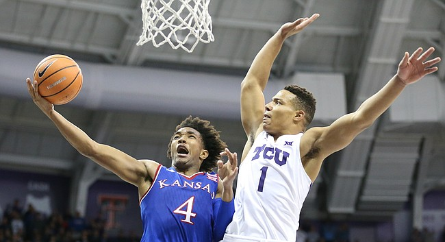 Kansas guard Devonte' Graham (4) goes to the bucket and is fouled hard by TCU guard Desmond Bane (1) late in the second half, Saturday, Jan. 6, 2018 at Schollmaier Arena.