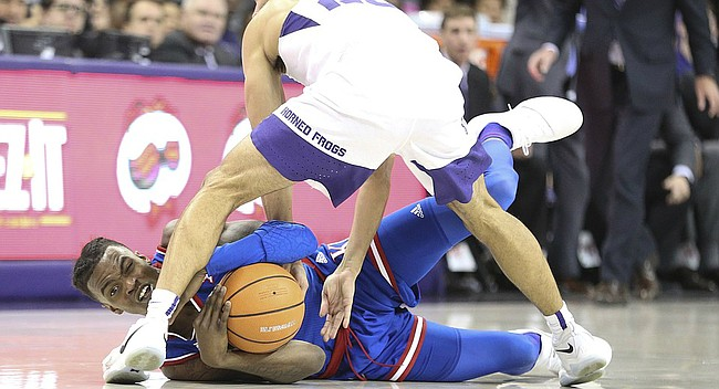 Kansas guard Lagerald Vick (2) wrestles for a ball with TCU guard Alex Robinson (25) during the second half, Saturday, Jan. 6, 2018 at Schollmaier Arena.