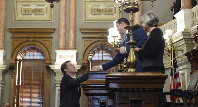 Gov. Sam Brownback shakes hands with House Speaker Ron Ryckman, R-Olathe, and Senate President Susan Wagle, R-Wichita, before delivering his eighth and final State of the State address.