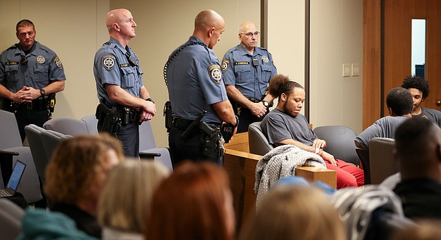 Members of the Douglas County Sheriff's Office stand near defendant Anthony L. Roberts Jr., seated at left, during a joint preliminary hearing, Thursday, Jan. 11, 2018, for three men charged in an October 2017 triple homicide on Massachusetts Street. At right are the two other defendants, Dominique J. McMillon, seated in back, and Ahmad M. Rayton.