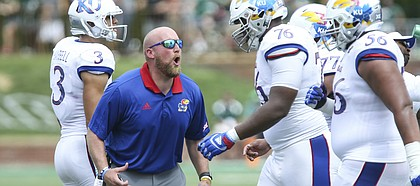 Kansas offensive line coach Zach Yenser yells at Kansas offensive lineman Chris Hughes (76) as he heads to the sidelines during the second quarter on Saturday, Sept. 16, 2017 at Peden Stadium in Athens, Ohio.