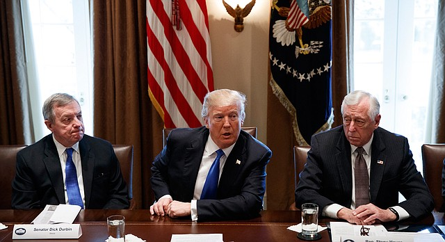 In this Jan. 9, 2017, photo, Sen. Dick Durbin, D-Ill., left, and Rep. Steny Hoyer, D-Md. listen as President Donald Trump speaks during a meeting with lawmakers on immigration policy in the Cabinet Room of the White House in Washington. (AP Photo/Evan Vucci)