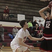 Lawrence High junior Brett Chapple looks to pass in the second half of the Lions' 72-64 win over Shawnee Mission North on Friday.