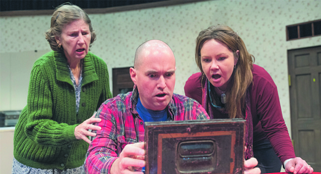 "Actor Brian Williams, as Jimmy Nowak, slowly opens a box of family letters as Carole Ries, left, playing Clara Nowak, and Hailey Gillespie, right, playing Ruth Nowak, watch in anticipation in a scene from the comedy ""Miracle on South Division Street"". The play opens Friday, Jan. 19, 2018 at Theatre Lawrence."