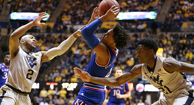 Kansas guard Devonte' Graham (4) is hounded by West Virginia guard Jevon Carter (2) and West Virginia forward Wesley Harris (21) during the first half, Monday, Jan. 15, 2018 at WVU Coliseum in Morgantown, West Virginia.