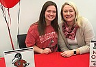 Free State senior Murphy O'Malley, left, signed to play college volleyball at Benedictine College on Wednesday in the FSHS conference room.